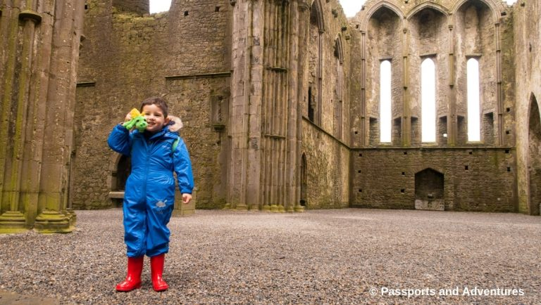 The Rock Of Cashel With Kids - Boy in blue rainsuit holding a green dragon in the Abbey.