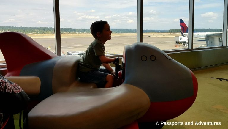 Awesome Tips For Flying With Babies and Toddlers - A toddler playing on a toy airplane in Portland airport children's play area
