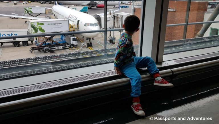 Awesome Tips For Flying With Babies and Toddlers - A toddler in pyjamas in an airport looking out the window at a plane