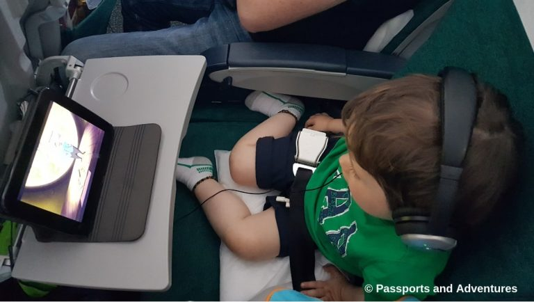 Awesome Tips For Flying With Babies and Toddlers - A toddler on an airplane watching a tablet