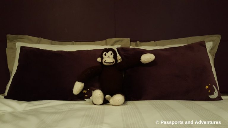 Awesome Tips For Flying With Babies and Toddlers - A Curious George monkey teddy bear sitting on a hotel bed