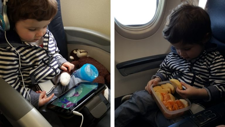 Awesome Tips For Flying With Babies and Toddlers - A Toddler eating snacks and watching a tablet on a plane