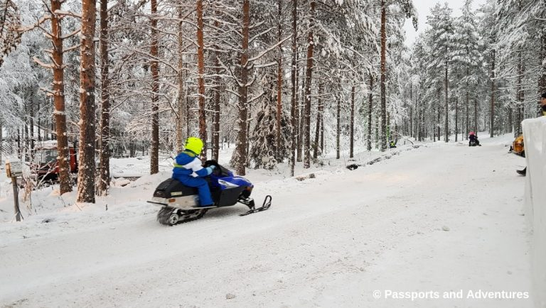 Awesome Things To Do In Rovaniemi With Kids - A boy on a snowmobile at Santa Claus Village.