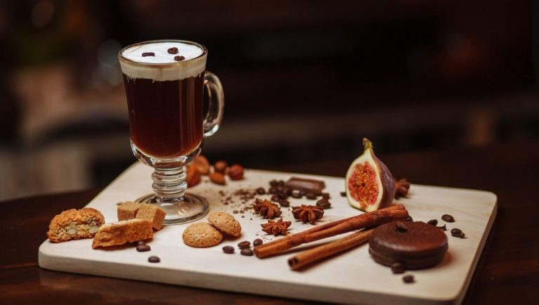 An Irish Coffee served with biscuits, chocolate and figs.