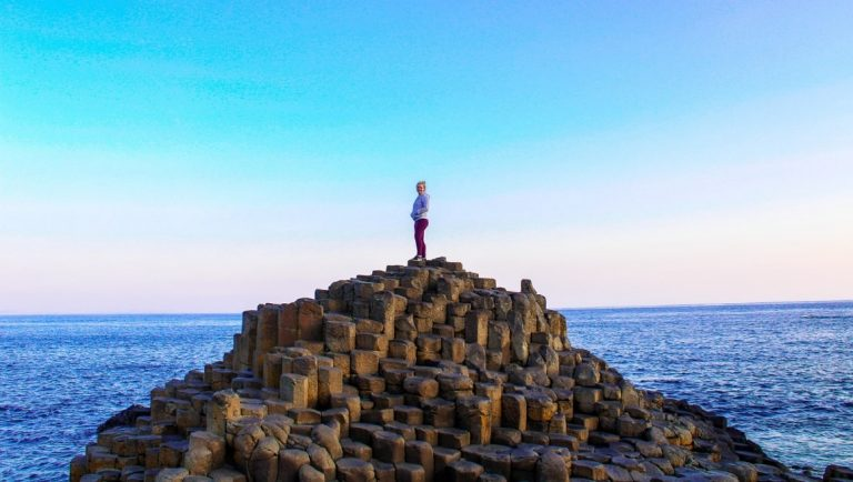 A girl on top of the Giant's Causeway, one of the top 10 things to do in Ireland.