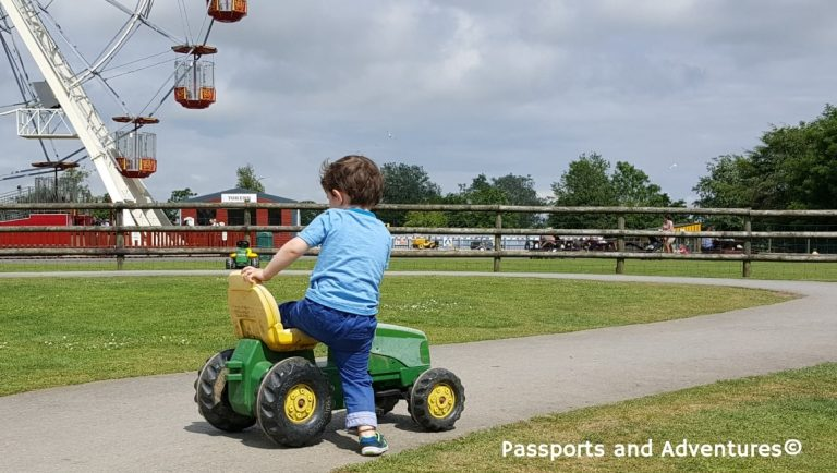 Boy getting onto a ride-on tractor at Folly Farm Adventure Park and Zoo