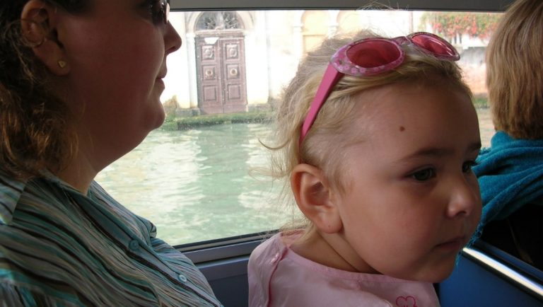 Young girl on her mum's lap in a boat on the water in Venice - What it's really like travelling with young kids