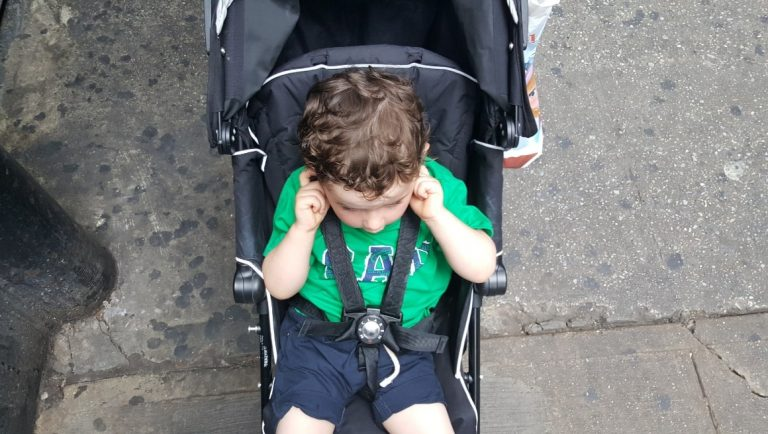 Young boy in a stroller with his fingers in his ears, avoiding the sirens of New York