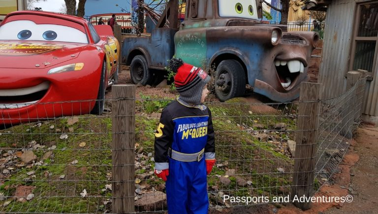 Boy standing in front of Lightning McQueen and Mater at the Car Quatro Rally Ride, which will delight young kids at Disneyland Paris.