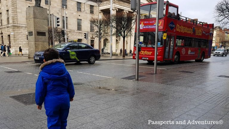 A young boy watching a City Sightseeing bus pass by on O'Connell Street, Dublin, Ireland