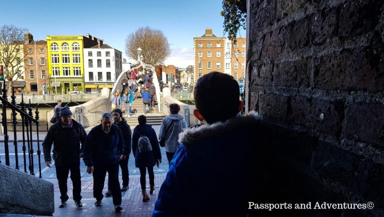 A young boy watching people crossing the Ha'Penny Bridge in Dublin, Ireland