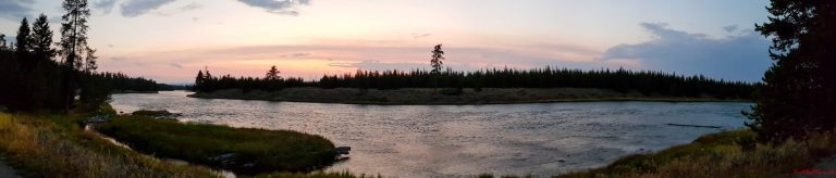 Sunset over the Madison River in Yellowstone with a sky full of red and pink hues