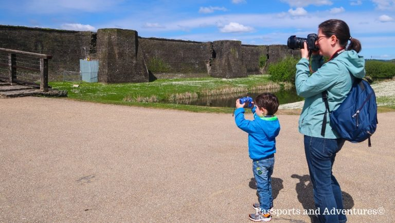 Mum and her son both taking pictures of a castle. Mum on her dslr, son on his toddler camera