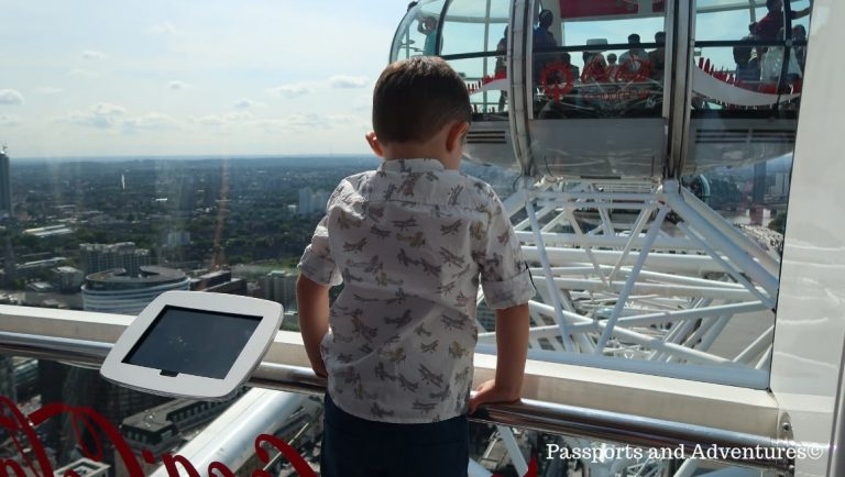 Toddler inside one of the London Eye Pods looking down onto the River Thames. The London Eye is one of the best London attractions for toddlers