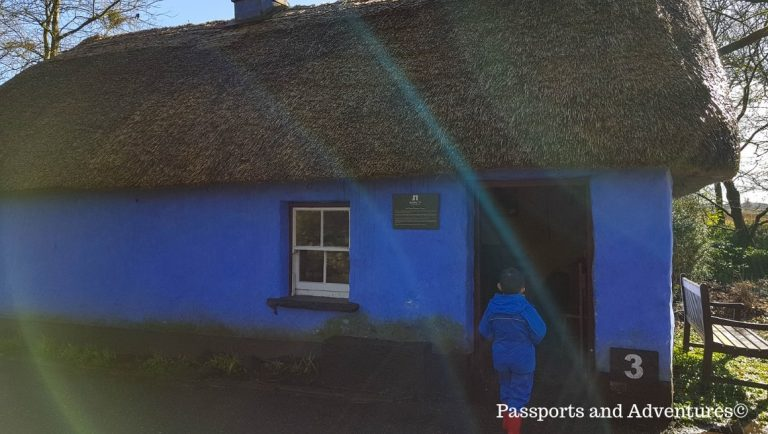 A young boy entering a blue, thatched-roofed house in the Folk Park at Bunratty Castle