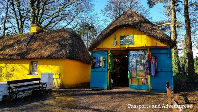 A blue and yellow thatched-roofed house in the Folk Park at Bunratty Castle, Ireland