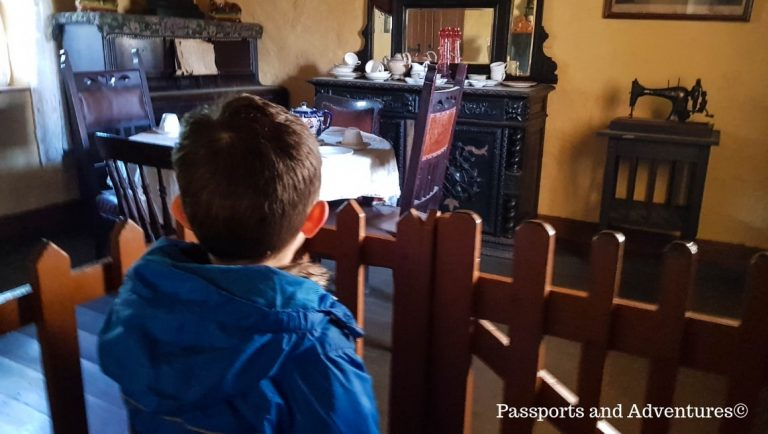 Little boy looking into a room furnished with old furniture at Bunratty Castle and Folk Park