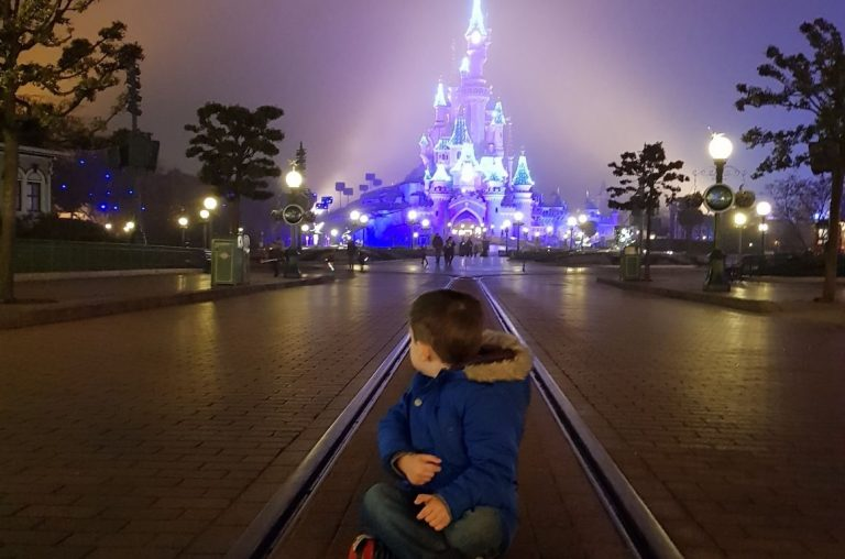 A young boy sat on the rail tracks in front of the Sleeping Beauty Castle at night in Disneyland Paris