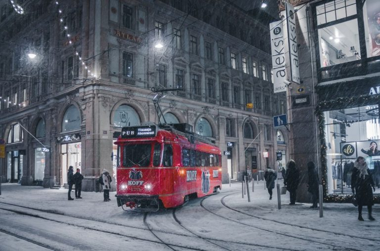 A tram in Helsinki in the dark, with the street lights on, with snow falling lightly around it
