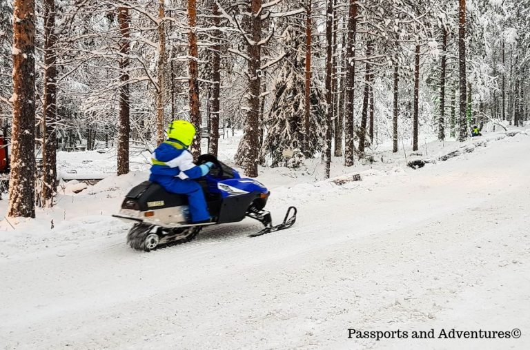 A young boy in a blue snowsuit riding a snowmobile in Santa Claus Village, Rovaniemi, Lapland