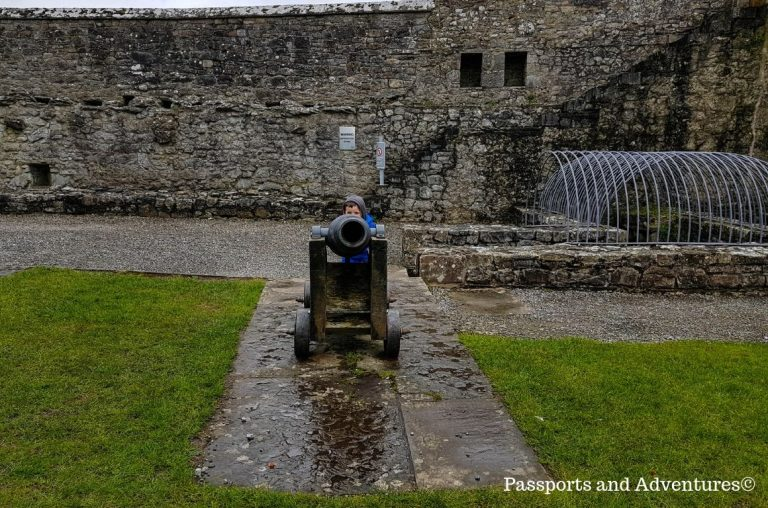 A young boy hiding behind one of the cannons at Cahir Castle, Tipperary, Ireland