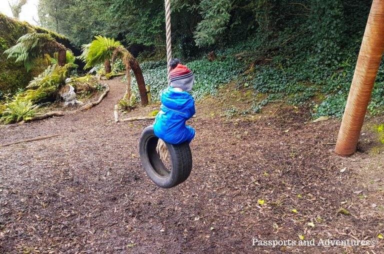 A young boy in a blue rainsuit swinging on a tyre swing in the playarea of Lismore Castle
