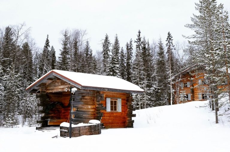 A log cabin covered and surrounded in crisp white snow in Lapland