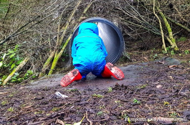 A young boy in a blue rainsuit and red welly boots, sitting backwards in front of a mucky tube slide