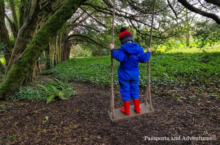 A young boy in a blue rainsuit and red wellington boots standing on a tree swing in Lismore Castle and Gardens