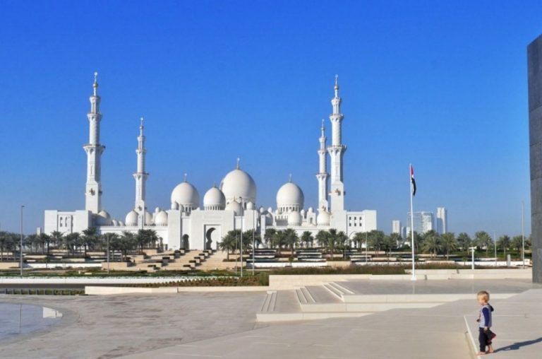 A boy standing in the foreground with the famous Sheikh Zayed Grand Mosque in the background, the Abu Dhabi grand mosque