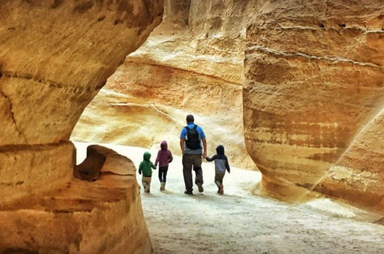 A family walking through the rocks on their way to Petra