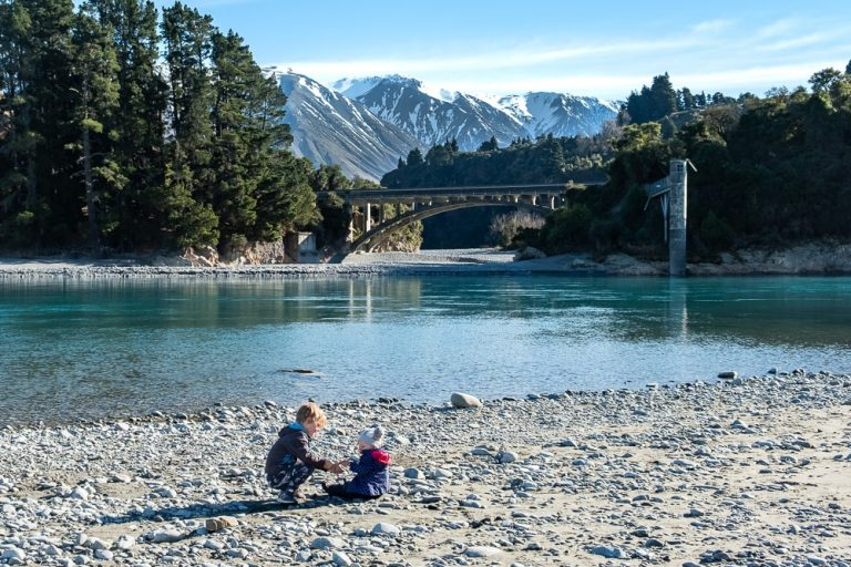 Two young children playing on a rocky shore in front of a bridge at Rakaia Gorge in New Zealand