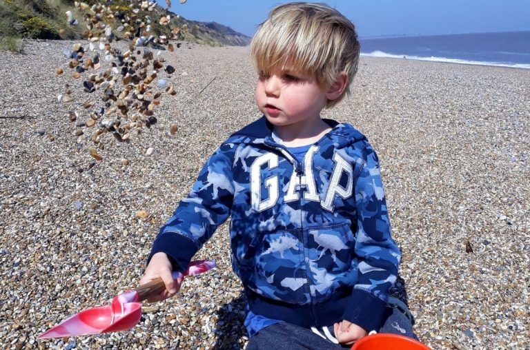 A young blonde boy on a stony beach, dressed in a blue GAP top, playing with a bucket and spade in the stones