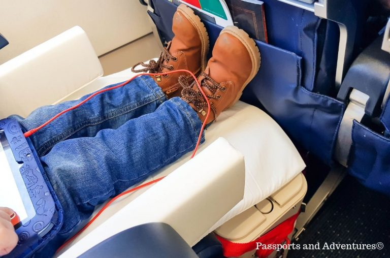 A picture of a young boys feet up on an airplane, helped by using the JetKids BedBox which turned his seat into a bed