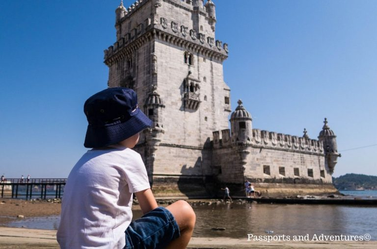 A young boy sitting on a step in front of Belem Tower in Lisbon. Boy has demin shorts, a white t-shirt and navy sun hat on