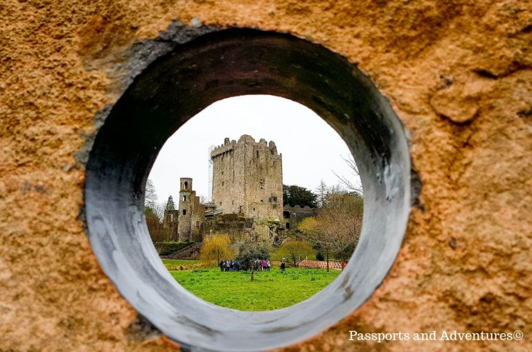 A picture of Blarney Castle taken through a round hole in a wall