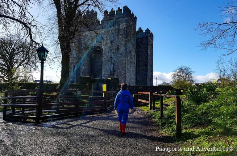 A small boy in a blue suit walking towards the Keep at Bunratty Castle, Ireland