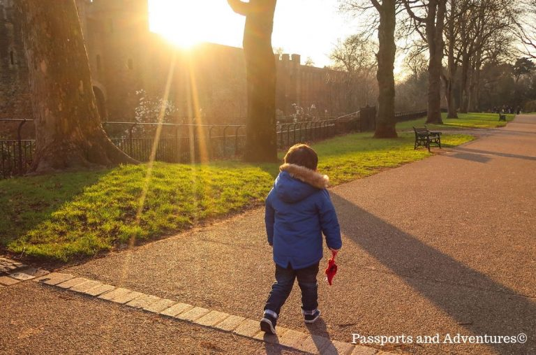 A little boy in a blue jacket walking along a path bathed in sunlight behind Cardiff Castle
