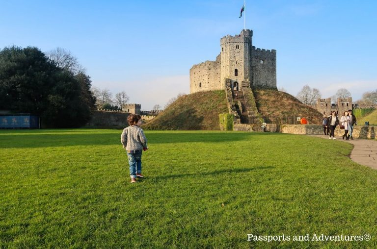 A little boy in jeans and a grey cardigan on the grass in front of the Norman Keep at Cardiff Castle