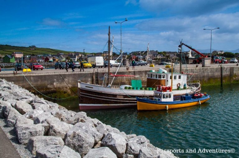 A small colourful fishing boat moored beside a larger one in Dingle Harbour in Ireland