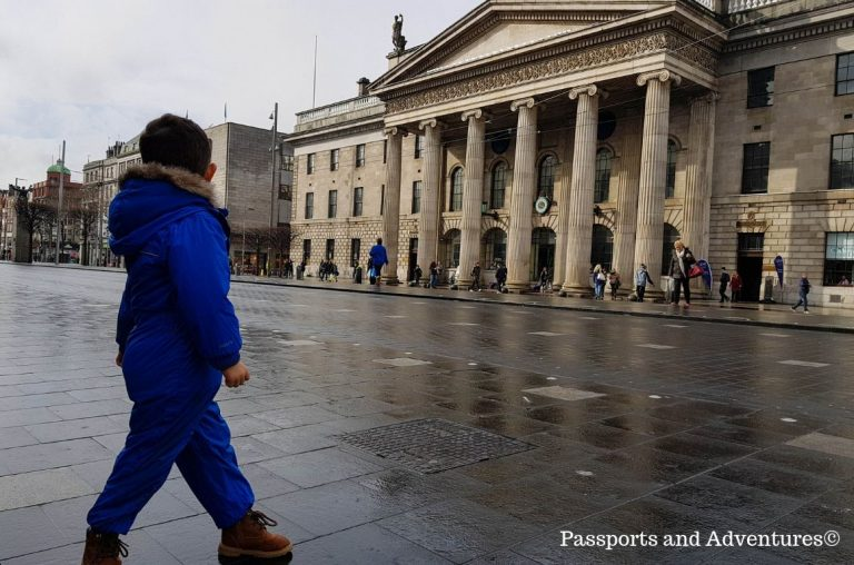 A little boy in a blue suit standing on O'Connell Street in Ireland looking at the GPO building