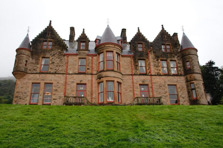 A picture of Belfast Castle with lush green grass in front of it
