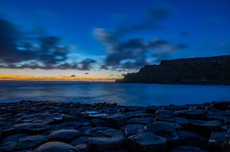 A scene from the Giant's Causeway in Northern Ireland with a blue, darkened sky above it