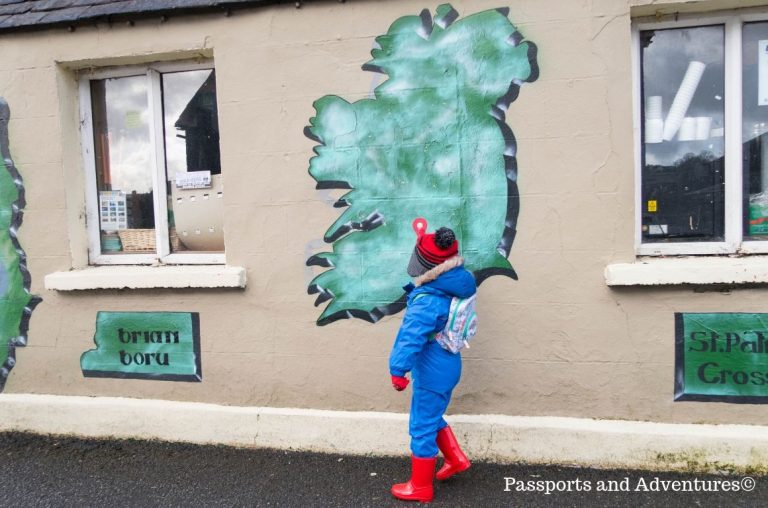 A little boy in a blue suit and red wellington boots pointing to a place on a map of Ireland on the side of a building