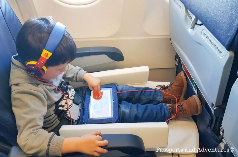 A young boy in his seat on an airplane with his legs up on the JetKids BedBox