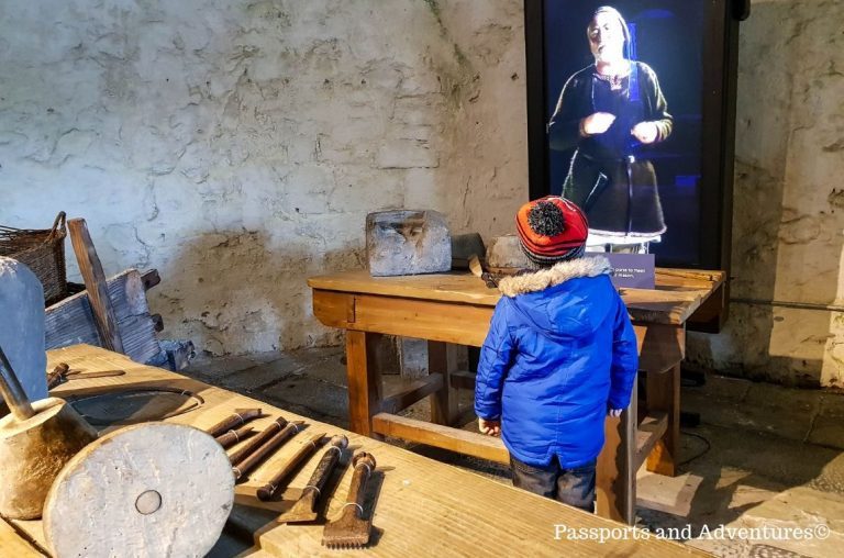 A little boy in a blue coat and red hat standing inside a tower in King Johns Castle, Limerick in front of a holographic display of a stonemason.