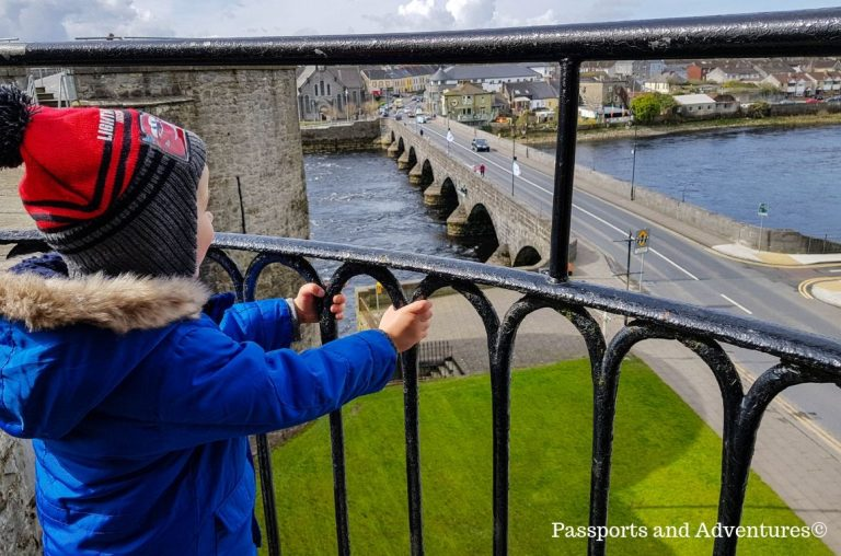 A little boy in a blue coat and red hat admiring the views across the River Shannon from King Johns Castle in Limerick, Ireland