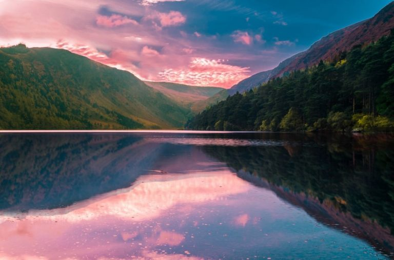 A lake in Ireland with a pink sky above it reflecting on the smooth water below