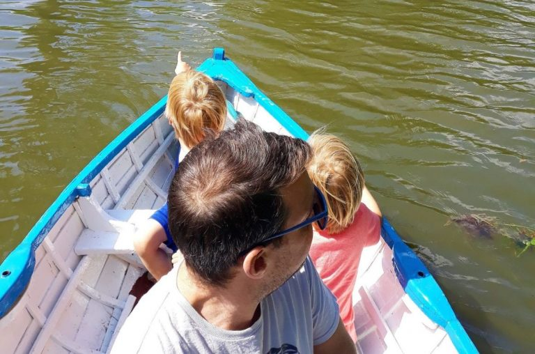 Family enjoying a boating ride on a lake in Suffolk