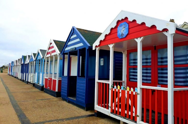 Colourful beach houses at Southwold in Suffolk in a mixture of red, blue and white with nautical themed paint work